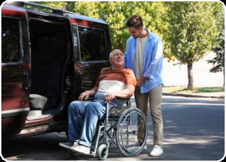 a man assisting a senior man in a wheelchair