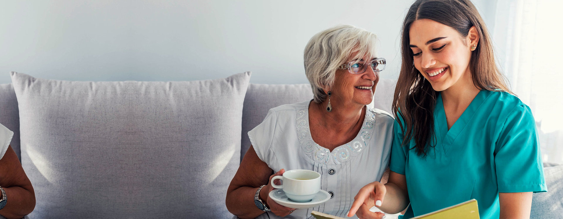 a caregiver and a senior woman looking at a photo album