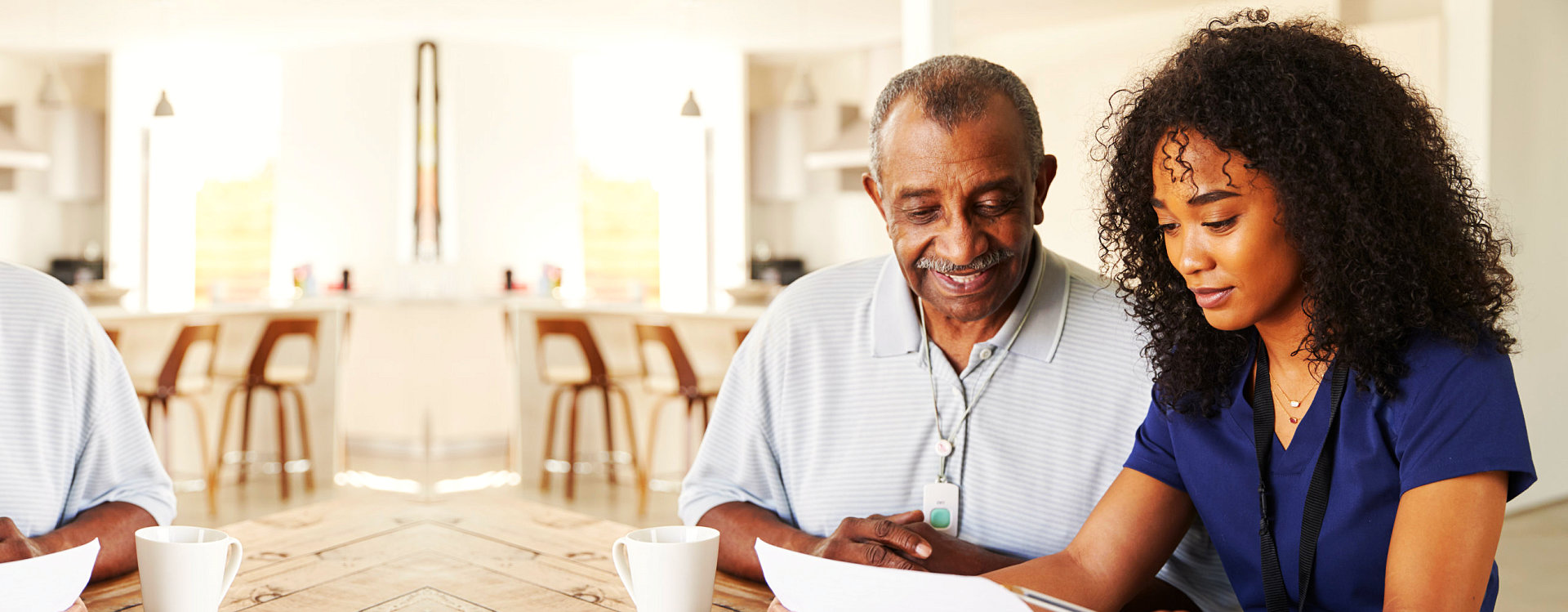 a caregiver helping a senior man fill out forms