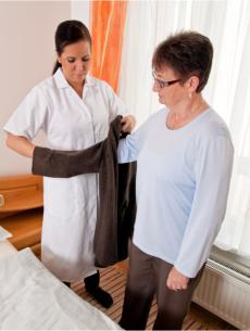 a caregiver assisting a senior woman get dressed