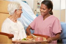 a caregiver serving food to a senior woman