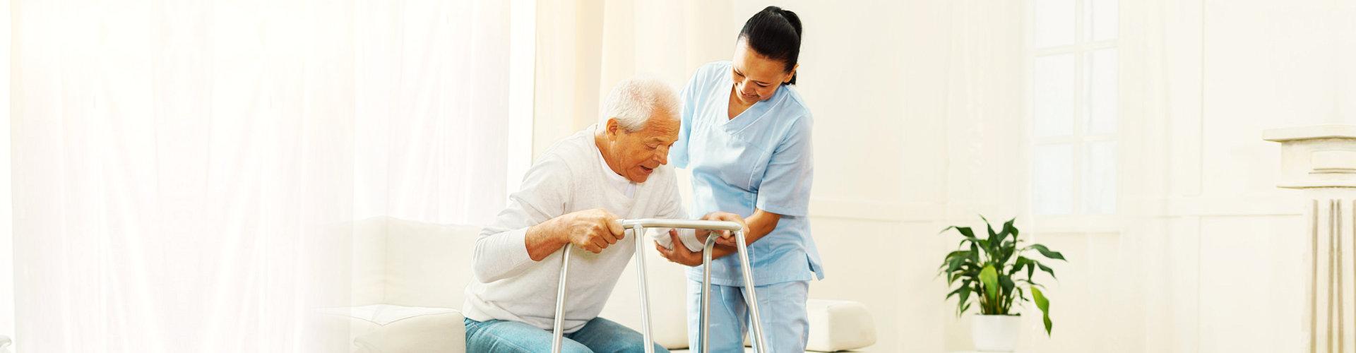 a caregiver assisting a senior man use a walker