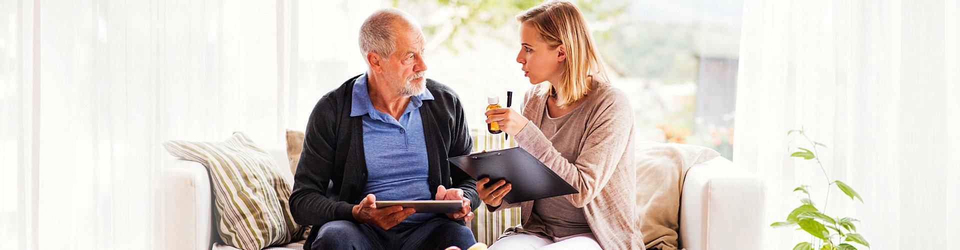 a caregiver reminding a senior man to take his medicine