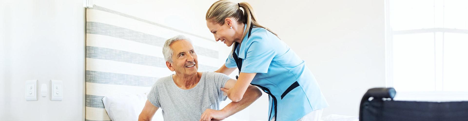 a caregiver assisting a senior man stand