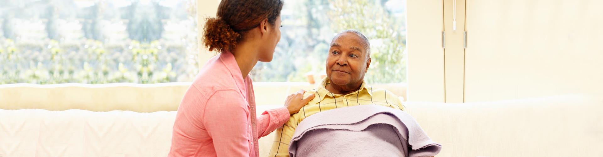 a caregiver and a senior man talking